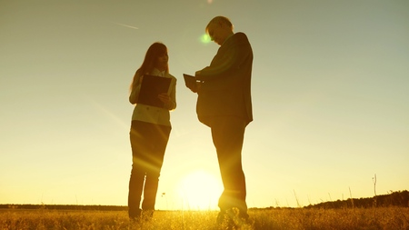 Business man with tablet and business woman with tablet discuss plan and schedule at sunset and laughs. Business meeting with working partner