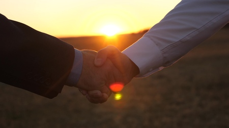 handshake at sunset . man in blue shirt and jacket and man in white shirt shake hands at sunset in rays of a beautiful sunset. close-up. 写真素材