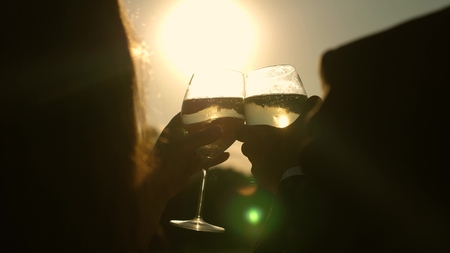 champagne sparkles and foams in sun. couple in love holding wine glasses with sparkling wine on background of sunset. closeup. teamwork of loving couple. celebrating success and victory. Slow motion