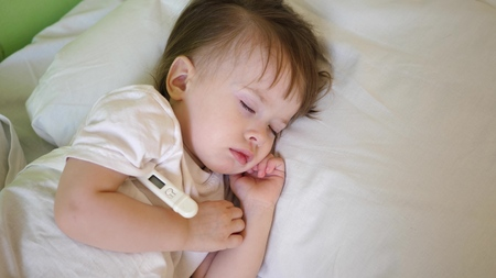 Small child sleeps in hospital ward on white bedding and measures temperature with thermometer. Treatment of children in hospital. Sick baby improves his health in hospital