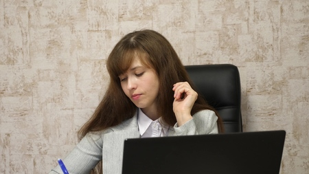 young female entrepreneur working behind laptop. online business conversation on computer. girl sitting in chair in office at computer and takes notes in notebook. secretary writes pen in notebook 스톡 콘텐츠