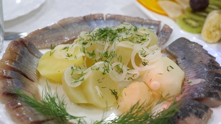 Sliced herring on a plate with boiled potatoes sprinkled with onion dill. server table in a restaurant. delicious food on the table. all inclusive Foto de archivo