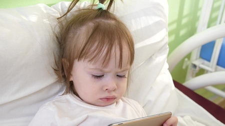 Cute little girl is lying on bed in childrens hospital, watching funny cartoons on the smartphone. Banco de Imagens