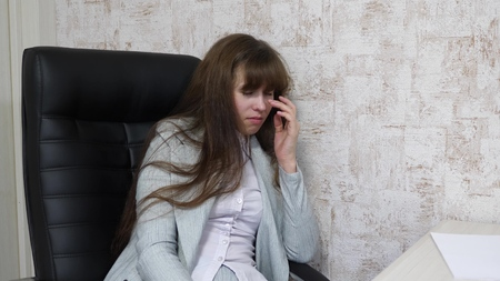 tired young business woman in her workplace. Woman office worker wipes tired eyes. irregular work schedule of an office worker