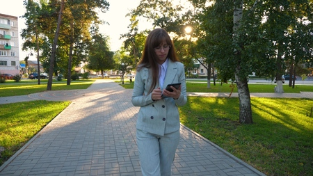 Sensual girl in a light business suit goes to work. beautiful business woman walking along the alley in the park with a tablet in her hands. Imagens