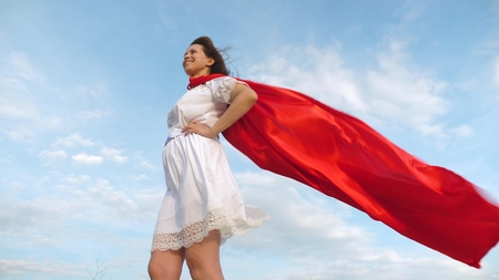 girl dreams of becoming a superhero. superhero girl standing on the field in a red cloak, cloak fluttering in the wind. young girl in a red cape dream expression