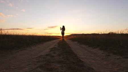 A business woman walks along a country road with a tablet in her hand, the sun miertsaet between womens legs. sexy business woman girl running in the countryside. sexy girl travels in the countryside.