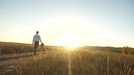 businessman in sunglasses goes down country road with a briefcase in his hand. agricultural business concept. The entrepreneur works in a rural area. farmer inspects the land at sunset. Slow motion