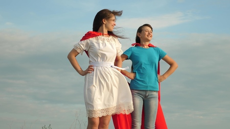 Mom and daughter play superheroes. two girls in red cloaks of superheroes stand against a blue sky, the wind inflates a cloak. happy family concept Banco de Imagens