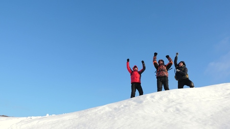 Travelers come to the top of a snowy hill and enjoy the victory against the blue sky. teamwork and victory. teamwork of people in difficult conditions. tourists travel in the snow in winter.