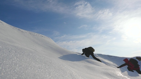 Teamwork Wunsch zu gewinnen. Kletterer erklimmen den Gipfel eines schneebedeckten Berges in Alaska. Reisende in der Arktis auf einem Hügel in den hellen Strahlen der Sonne. Sibirien-Konzept des Sporttourismus. Standard-Bild