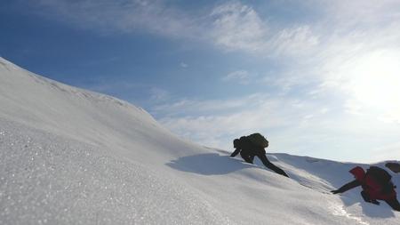 travail d'équipe désir de gagner. Des alpinistes grimpent au sommet d'une montagne enneigée en Alaska. voyageurs dans l'Arctique sur une colline sous les rayons brillants du soleil. Concept de Sibérie de tourisme sportif. Banque d'images
