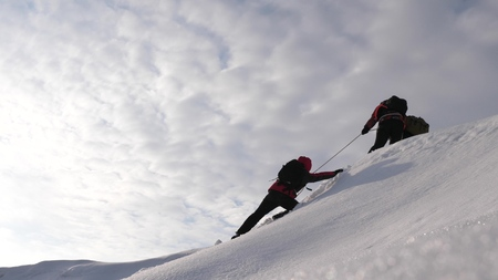 three Alpenists in winter climb rope on mountain. Travelers climb rope to their victory through snow uphill in a strong wind. tourists in winter work together as team overcoming difficulties.