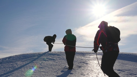 team of business people climb to the top of their success. teamwork business people. three climber climb rope on snowy mountain. people work together to overcome difficulties. Stockfoto