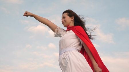 girl dreams of becoming a superhero. beautiful superhero girl standing on a field in a red cloak, cloak fluttering in the wind. Slow motion. young woman plays in a red cloak with expression of dreams.