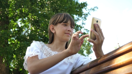 Young millennial woman in the Arboretum, making gestures on the phone display. A young girl using a smartphone is writing a letter on a bench in a beautiful green park. Stock fotó