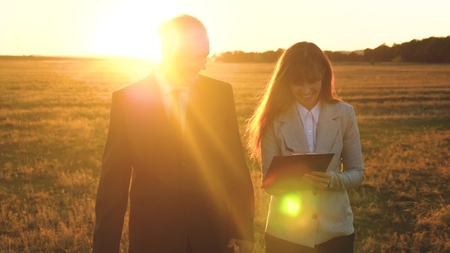 teamwork of business people.businessman and businesswoman discuss teamwork plan in the park at sunset. team of business people go to victory and success. teamwork and victory. yellow sunset