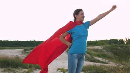 girl dreams of becoming a superhero. beautiful girl superhero standing on the field in a red cloak, cloak fluttering in the wind. Slow motion. young girl walks in a red cloak expression of dreams Reklamní fotografie
