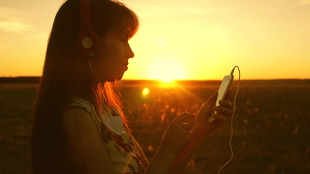 girl listening to music and dancing in the rays of a beautiful sunset. a young girl in headphones and with a smartphone touches finger to the sensor of the tablet selects songs online. Slow motion. Banco de Imagens