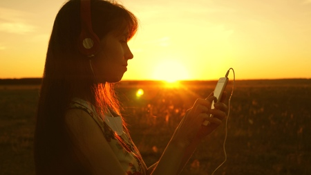 girl listening to music and dancing in the rays of a beautiful sunset. a young girl in headphones and with a smartphone touches finger to the sensor of the tablet selects songs online. Slow motion. 版權商用圖片