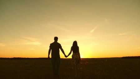 Young couple in love walking across the field holding hands. girl and man go to the sunset. happy family walks in the park in summer in the rays of the sun. happy family concept Stock fotó