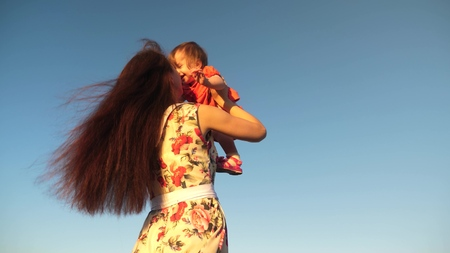 Mom throws her daughter up to the sky. mother plays with a small child against a blue sky. happy family playing in the evening against sky. mother throws up the baby, baby smiles. slow motion filming.