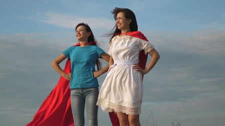 two girls in red cloaks of superheroes stand against a blue sky, the wind inflates a cloak. Mom and daughter play superheroes. happy family concept Banco de Imagens