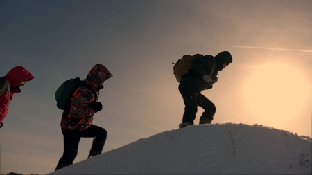 teamwork of business people. three climbers climb one after another on a snow-covered hill. team of business people go to victory and success. people work together to overcome difficulties.
