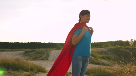 beautiful girl superhero standing on the field in a red cloak, cloak fluttering in the wind. Slow motion. A young girl dreams of becoming a superhero. girl walks in a red cloak expression of dreams