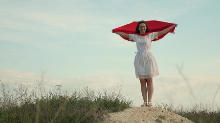 funny and funny woman plays hero in a cloak of red cloak. girl dreams of becoming a superhero. beautiful superhero girl standing on a field in a red cloak, cloak fluttering in the wind.
