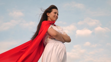 superhero girl standing on the field in a red cloak, cloak fluttering in the wind. close-up. girl dreams of becoming a superhero. young girl in a red cape dream expression