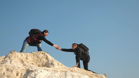tourists give hand to each other, climbing to top of the hill. team of male travelers goes to victory and success. teamwork of business people. three climbers climb one after another on white rock.