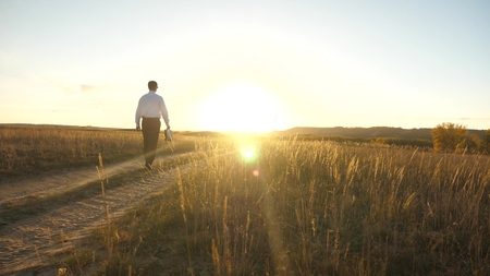 businessman in sunglasses goes down the country road with a briefcase in his hand. The entrepreneur works in a rural area. a farmer inspects the land at sunset. agricultural business concept. 版權商用圖片