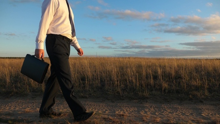 businessman in sunglasses goes down the country road with a briefcase in his hand. The entrepreneur works in a rural area. a farmer inspects the land at sunset. agricultural business concept.