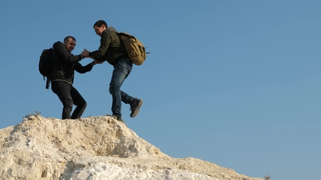 teamwork of business people. tourists give hand to each other, climbing to top of the hill. team of male travelers goes to victory and success. two climbers climb one after another on white rock.
