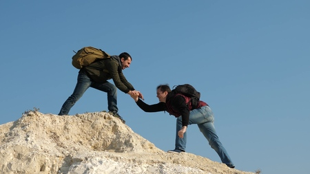 two climbers climb one after another on white rock. teamwork of business people. tourists give hand to each other, climbing to top of the hill. team of male travelers goes to victory and success.