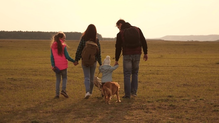 dad, mom, daughters and pets, tourists. teamwork of a close-knit family. the family travels with the dog across the plains and mountains. The concept of a sports family holiday in nature. Banco de Imagens