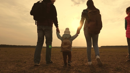 Dad, Mom, a small child and daughters and pets tourists. teamwork of a close-knit family. family travels with the dog on the plain. The concept of a sports family holiday in nature.
