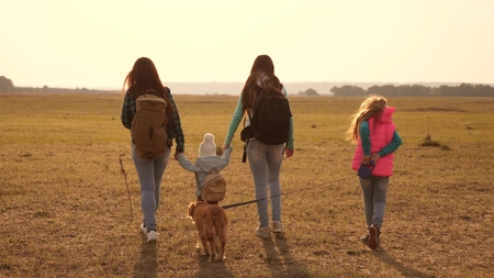 family travels with the dog across the plains and mountains. mother, daughters and home pets tourists. teamwork of a close-knit family. The concept of a sports family holiday in nature.