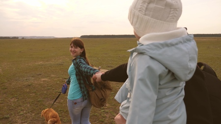 family travels with dog on plain. come after me. Dad with a small daughter in his arms travels with children and a pet. eldest daughter and father of tourists go hand in hand and smile.