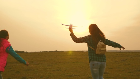 children play toy airplane. Happy girl sisters run with a toy plane at sunset on the field. The concept of a happy family. Girls dream of flying and becoming a pilot. Slow motion