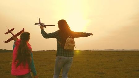 children play toy airplane. Happy girl sisters run with a toy plane at sunset on the field. The concept of a happy family. Girls dream of flying and becoming a pilot. Slow motion 版權商用圖片
