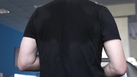 sweaty back men in T-shirt close-up. fitness club man engaged in walking. strengthening muscles of heart and legs by walking. cardio load. man trains on treadmill. walking in gym. weight loss in gym. Stockfoto