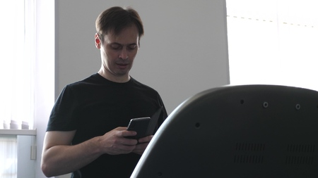 man on a treadmill is in his hand smartphone. fitness club man engaged in walking. strengthening the muscles of heart and legs by walking. cardio load. walking in gym. weight loss in gym. Banco de Imagens