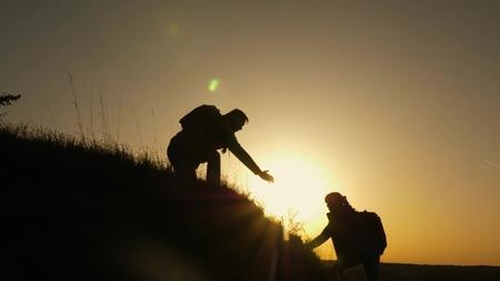 Reisender Mann streckt seine Hand zu einem Mädchen aus, das auf die Spitze eines Hügels klettert. Reisende erklimmen die Klippe, die Hand hält. Teamarbeit von Geschäftsleuten. Glückliche Familie im Urlaub. Touristen umarmen sich auf dem Berg Standard-Bild