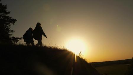 familie moeder en dochter reizen vakantie. Vrouw met opgeheven handen bovenop een berg die zonsondergang bekijkt. Hiker Girl steekt haar hand op, viert de overwinning en geniet van prachtige landschappen en natuur. Stockfoto