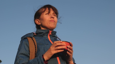 traveler woman drinking hot tea and watching sunset against blue sky. girl tourist, stands on top of hill drinking coffee in a glass   . Adventurer rest after reaching goal. freedom concept. Banco de Imagens
