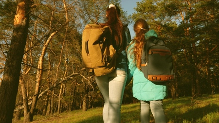 mother and daughter travelers walking through the woods with a backpack. Hiker Girs in a pine forest. The tourist enjoys life and nature. vacation adventure travel. Happy family travels. Banco de Imagens