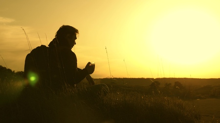 lonely traveler sitting on top of a hill drinking coffee   . tourist drinks hot tea and watches sunset. rest after reaching the goal. concept of freedom and dreams. world without borders