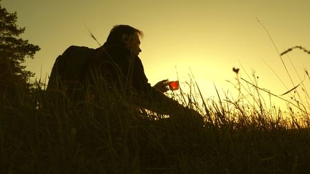 tourist drinks hot tea and watches sunset. lonely traveler sitting on top of a hill drinking coffee   . rest after reaching goal. concept of freedom and dreams. world without borders